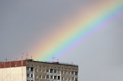 Bright multi-colored wide colorful rainbow after the storm in the gray sky above the town houses Stock Photo