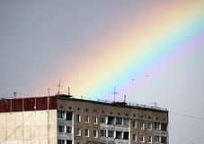 Bright multi-colored wide colorful rainbow after the storm in the gray sky above the town houses Royalty Free Stock Photography