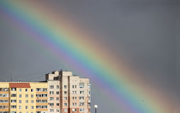 Bright multi-colored wide colorful rainbow after the storm in the gray sky above the town houses Royalty Free Stock Photos