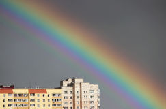 Bright multi-colored wide colorful rainbow after the storm in the gray sky above the town houses Stock Photos