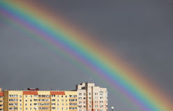 Bright multi-colored wide colorful rainbow after the storm in the gray sky above the town houses Stock Photography
