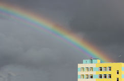 Bright multi-colored wide colorful rainbow after the storm in the gray sky above the town houses Stock Image