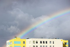 Bright multi-colored wide colorful rainbow after the storm in the gray sky above the town houses Royalty Free Stock Photo