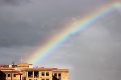 Bright multi-colored wide colorful rainbow after the storm in the gray sky above the town houses Royalty Free Stock Image