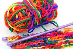 Bright multi-coloured colorful knitting wool or yarn with knitting needles on white background.  stock photo
