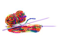 Bright multi-coloured colorful knitting wool or yarn with knitting needles on white background.  royalty free stock photos