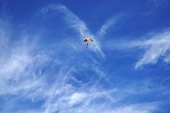Bright multicolor parachute canopy and skydivers silhouettes against the background of a blue sky stock photography