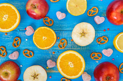 Bright multicolored background with citrus lemon, orange, cutting the apples, jelly sweets. In the shape of a heart and pretzels on a blue board Stock Photo
