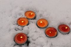 Bright multicolored candles burn in the snow Royalty Free Stock Photos
