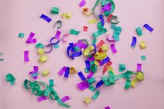 Bright multicolored confetti on a pink background. Multicolored paper confetti on a pink background. Birthday party concept stock photography