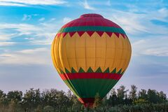 A bright multicolored hot air balloon at the moment of light touch with the ground on a forest lawn against a blue sky during suns