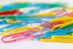 Bright multicolored office paperclips on white desktop close up Royalty Free Stock Image