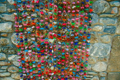 Bright multicolored ribbons/adornment/decoration. Bright multicolored ribbons/adornment/decoration hanging on the stone wall Stock Photos