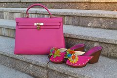 Bright neon pink pair of women`s shoes with handbag on a marble stairs Stock Image