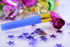 Bright New Year Party Decorations. Happy New Year party decorations with stars and noise maker, closeup Royalty Free Stock Photos