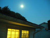 Bright at Night. The moon glows above a lamp-lit house royalty free stock images
