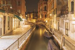 Bright night in Venice. View to water channel with bright illumination in Venice by night stock image