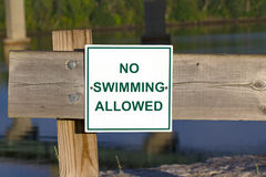 No Swimming sign on fence Stock Images