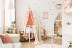 Nursery room with dots. Bright nursery room interior with white crib, decoration, poster and gold dots on the wall royalty free stock images
