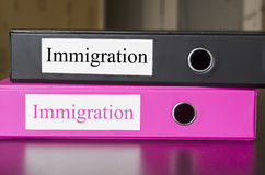 Bright office folders. Over dark background and immigrations text concept Stock Photos