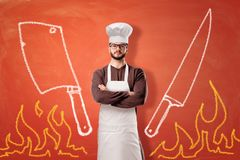 A bright orange background with drawn flames, a cleaver, a knife and a serious male cook standing in the center. stock images