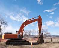 Bright Orange Backhoe in a Rural Area Royalty Free Stock Image