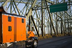 Bright orange big rig semi truck with extra space cab going on a Stock Photography