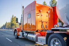 Bright orange big rig semi truck transporting tank semi trailer for transportation of liquid and liquefied chemical cargo running. Bright orange big rig American stock photography