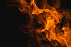 Bright burning fire on the black background. Bright orange burning fire on dark background. Abstract natural backdrop with different shapes of flame Royalty Free Stock Photos