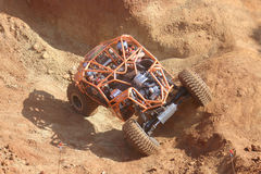 Bright orange car negotiating obstacles in dugout. Top view. Stock Image