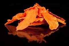 Bright, orange, crunchy, crisp snack of ripe and sweet pumpkin on a black backgroun stock photography