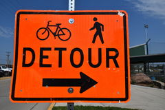 Detour sign instructs bikers and walkers. A bright orange detour sign instructs bikers and pedestrians Royalty Free Stock Photo