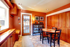 Bright orange dining room with black wooden table set Royalty Free Stock Photos