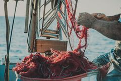 Bright orange fishing net with floats. Fisher boat in a sea. Hands of an old fisherman Stock Photos