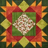 Bright orange-green geometric patchwork block from pieces of fabrics. Detail of quilt royalty free illustration