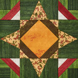 Bright orange-green geometric patchwork block from pieces of fabrics, detail of quilt Royalty Free Stock Photo