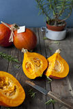 Bright orange hokkaido pumpkins. Vibrant orange chopped pumpkins exposing the pulp. They are on rural wooden table surrounded with herbs and plants. Shallow Stock Images