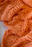 Bright orange Knitted plaid on a wooden background Stock Photos