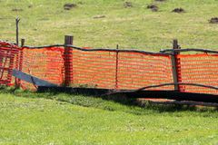 Bright orange makeshift improvised fence made of nylon net and wooden poles surrounded with uncut grass and molehills. On warm sunny spring day royalty free stock photography