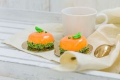 Bright orange mousse cakes and cup of coffee on white wooden tray Stock Photo