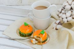 Bright orange mousse cakes and cup of coffee on white wooden tray Royalty Free Stock Photo