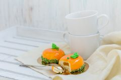 Bright orange mousse cakes and cup of coffee on white wooden tray Stock Image