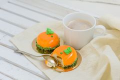 Tasty orange mousse cakes and cup of coffee on white wooden tray Royalty Free Stock Images