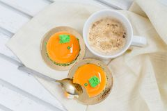 Tasty orange mousse cakes and cup of coffee on white wooden tray Royalty Free Stock Photo