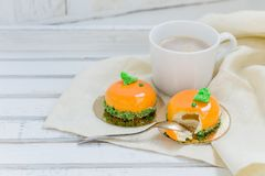 Bright orange mousse cakes and cup of coffee on white wooden tray Royalty Free Stock Image