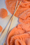 Bright orange plaid knitted, knitting needles and yarn balls Royalty Free Stock Photography