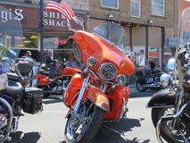 Bright Orange or Red Motorcycle at Sturgis, SD, motorcycle rally. Riders, pedestrians and motorcycles on the street during the Sturgis, South Dakota 77th Annual Stock Image