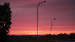 Bright orange-red sun rises over road, electro transmission lines, buildings and trees. stock video