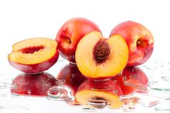 Peaches whole and cutted into two halves in water drops on white background isolated close up royalty free stock photography