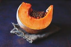 Bright orange slice of pumpkin with seeds on a napkin stock photo